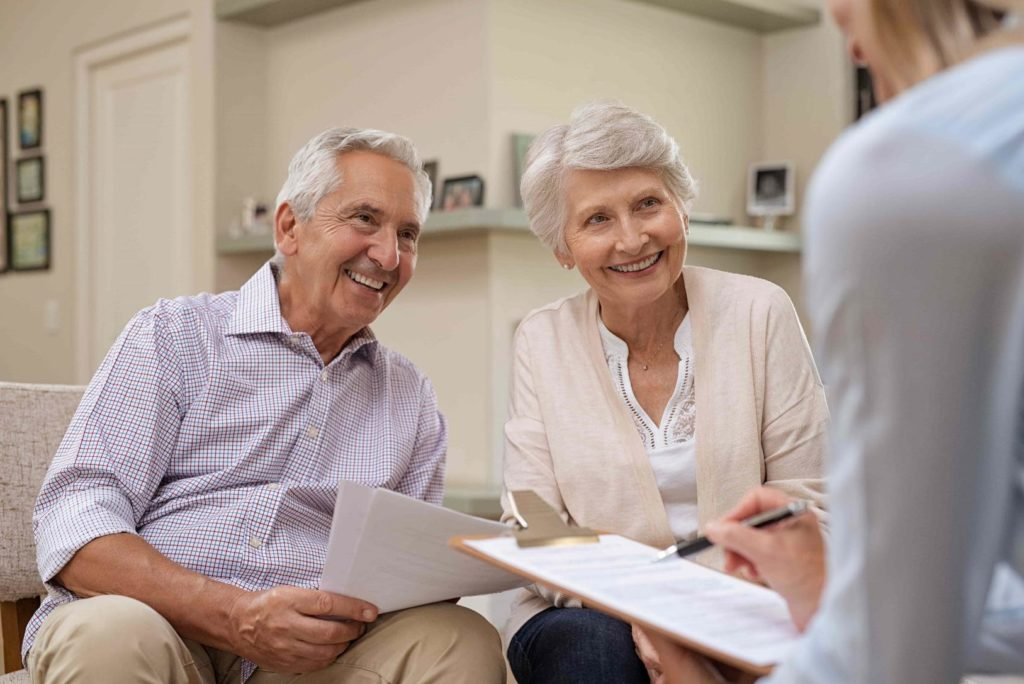 Elderly couple smiling at lawyer out of frame holding paperwork.