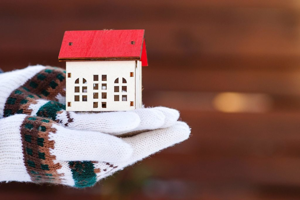 Gloved hands holding a house model in winter